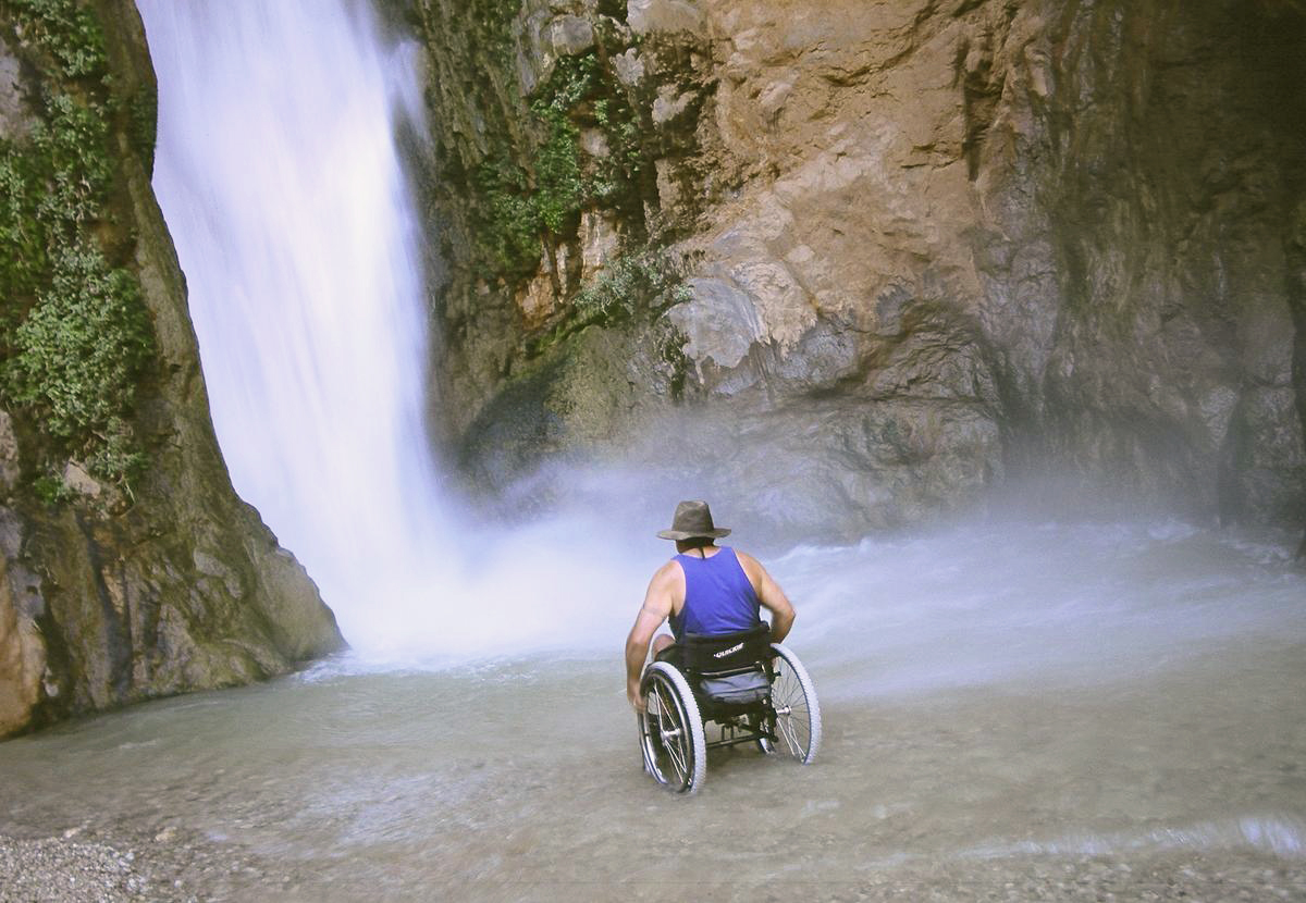 man facing waterfall in wheelchair